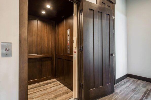 Home elevator with wooden walls and door
