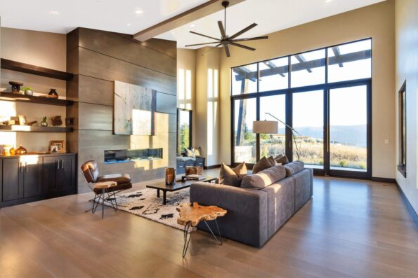 A living space with ceiling fan and wide glass doors