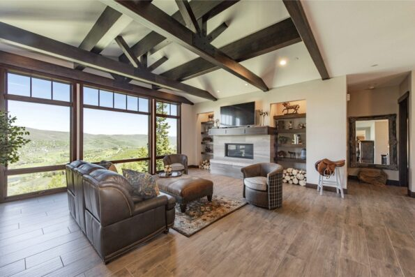 A living space with TV, fireplace, and a set of leather chairs