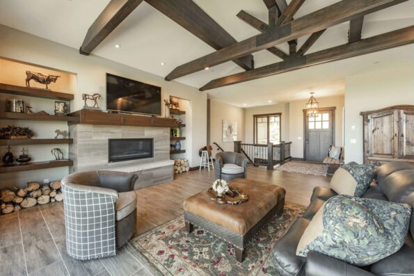 A living space with wooden beams, television, and fireplace