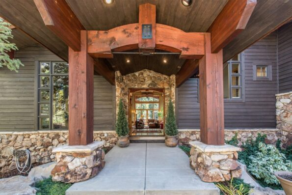 A grand entryway of a home with stones and wood panels