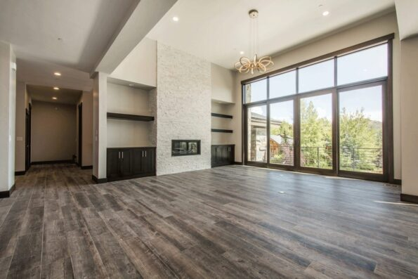 A wide home space with storage units, tall glass windows, and a fireplace