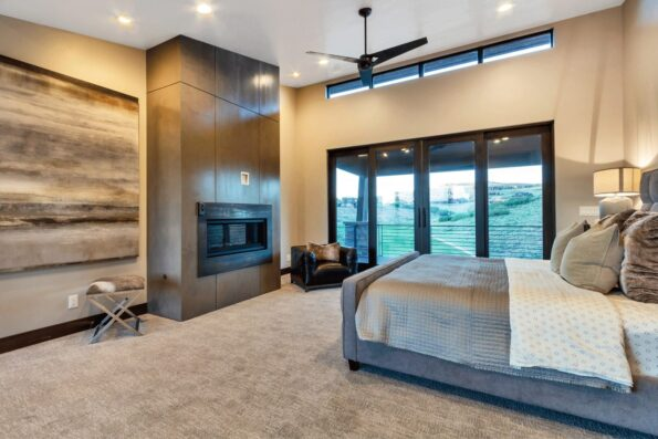 A bedroom with wide glass doors and ceiling fan