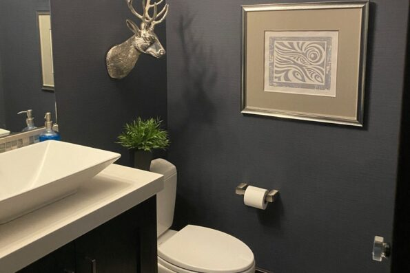 A black bathroom with white sink and toilet