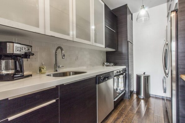 A kitchen with oven, coffee-maker, and sink