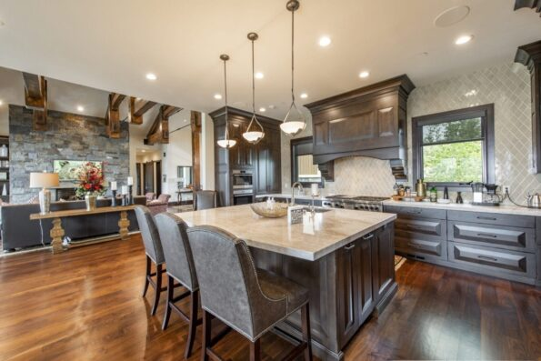 a kitchen with a big island with three tall chairs