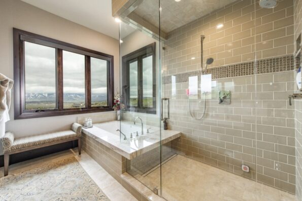 A bathroom with shower, bathtub, and lounge chair
