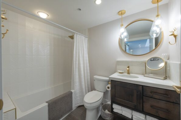 A white bathroom with gold mirrors and accessories