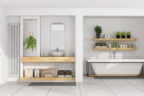 An all-white bathroom with wooden shelving units